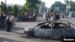 Residents walk past a burnt-out car following the unrest in the eastern Uzbek town of Andijon on May 13, 2005.