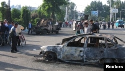 Residents pass burnt-out cars after the unrest in the eastern Uzbek town of Andijon on May 13, 2005.