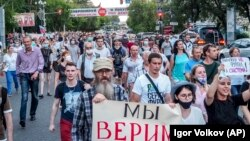 "People hold posters saying ""We trust Sergei Furgal"" during a protest in support of the forner governor in Khabarovsk on July 21."