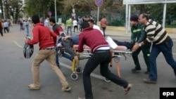 مصريون ينقلون مصاباً في إنفجار بجامعة القاهرة