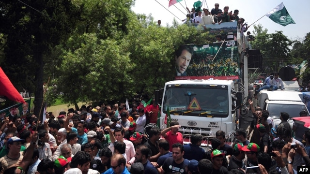 Pakistani cricketer-turned-politician Imran Khan (on truck, center) heads a protest march from Lahore to Islamabad against the government, in Lahore, on August 14.