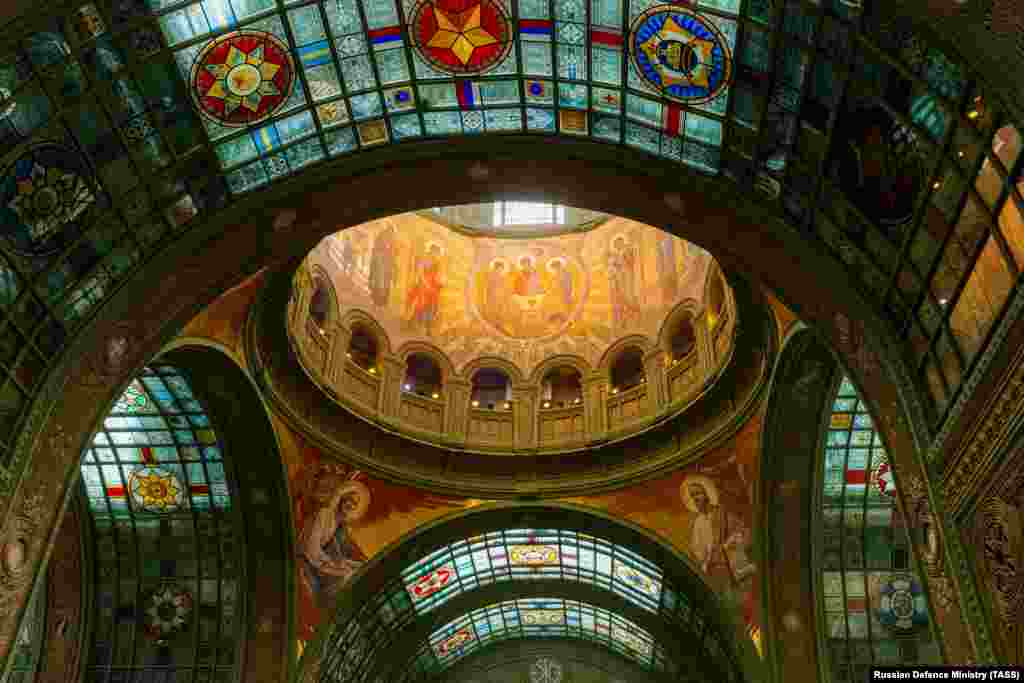 A shot of the interior of the church under the main dome shows a stained-glass emblem in the top right that features the communist hammer and sickle.