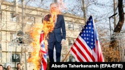 Iranian hardliners burn a cutout poster depicting British ambassador to Iran Robert Macaire along with British and U.S. flags during a memorial for passengers of Ukraine airplane, at the Tehran University in Tehran, January 14, 2020