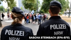 FILE: German Police officers watch demonstrators gathering to protest against the German asylum policy at the Ministry for Children, Family, Refugees and Integration of North Rhine-Westphalia (NRW) in Duesseldorf (July 2018).