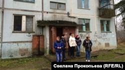 Ukrainian refugees stand outside one of the gloomy apartment buildings situated amid abandoned barracks at the former Russian air base in Smuravyevo. Local authorities are eager to see the 120 vacant flats rented out.
