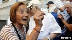 O pensionară la Atena, primind numărul de rând pentru ridicarea pensiei, la o filială a Băncii Naţionale a Greciei, 1 iulie 2016.