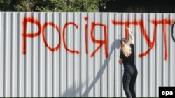 "An activist sprays the words ""Russia is here"" on the barrier around Inter TV in Kyiv on September 5."