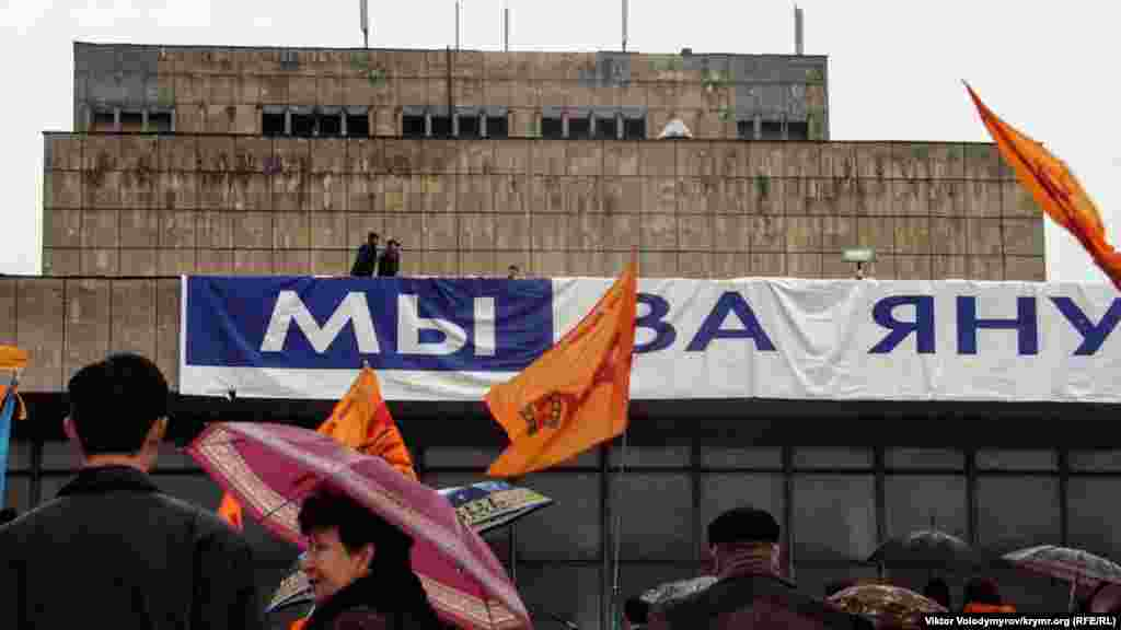 """Akimiyet namzetiniñ tarafdarları, Ukrain muzıkalı teatrniñ binasına """"Mı za Yanukoviça"""" (""""Biz Yanukoviç içün"""") yazısını asmağa tırışa, amma şiddetli yel olarğa keder etti."""