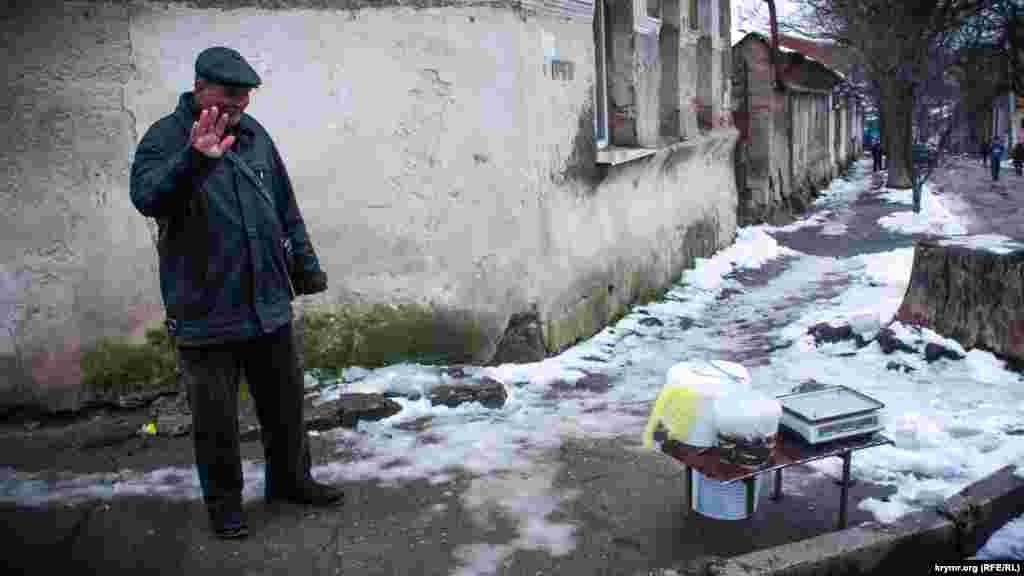 Чоловік продає рибу прямо на перехресті двох вулиць