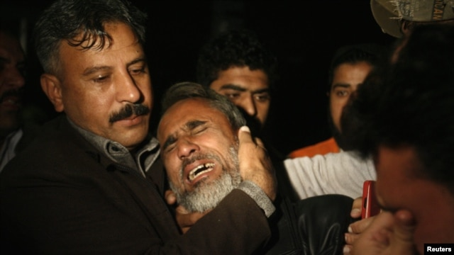 A man is comforted by his family as he mourns his brother, who was killed in the blast.