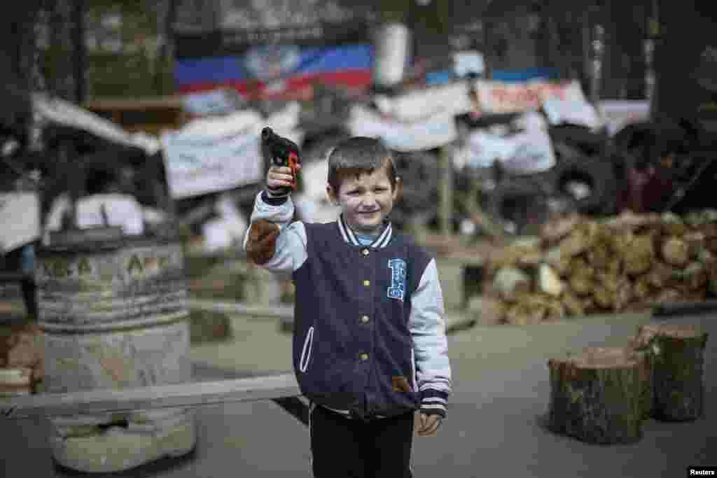 A boy with a toy gun poses for picture in front of barricades at police headquarters in the eastern Ukrainian town of Slovyansk. (Reuters/Gleb Garanich)