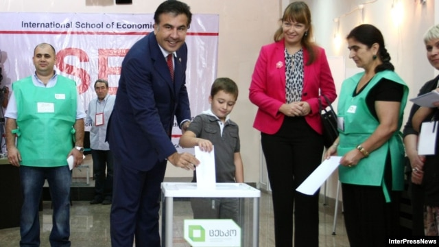 Georgia -- President Mikheil Saakashvili, accompanied by his wife Sandra Roelofs and son Nikoloz, casts his vote during a parliamentary election at a polling station in Tbilisi, 01Oct2012