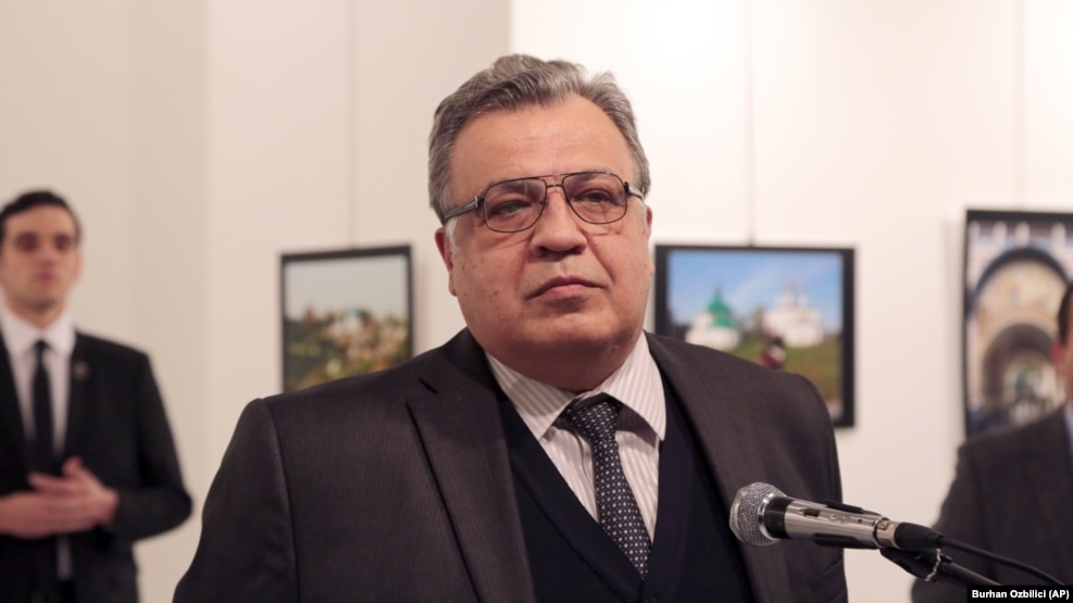 Russian Ambassador to Turkey Andrei Karlov speaks at a gallery in Ankara on December 19, just before a gunman (left) opened fire.