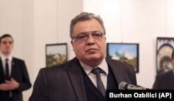 Russian Ambassador to Turkey Andrei Karlov speaks at a gallery in Ankara on December 19, just before the gunman (left) opened fire.