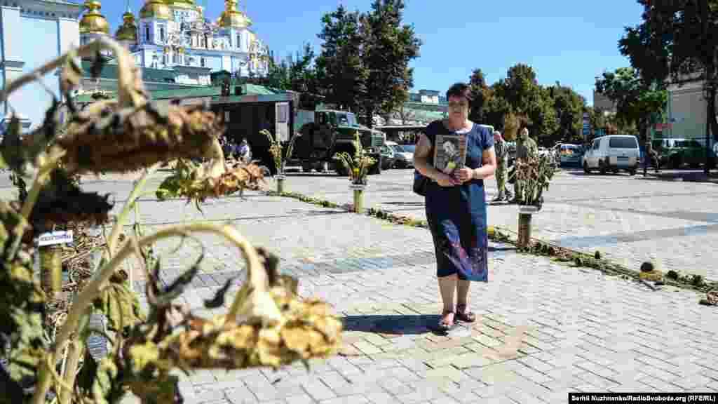 Мама з портретом сина проходить по символічному «зеленому коридору» з назвами населених пунктів, через які виходили війська з Іловайська, де їх обстрілювали російські війська