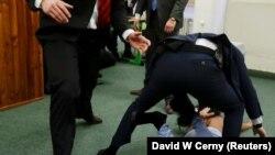 Сайлау учаскесінде Чехия президенті Милош Земанға шабуылдамақ болған Femen белсендісін күзетшілер жерге жығып, әкеткелі жатқан сәті. Прага, 12 қаңтар 2018 жыл.