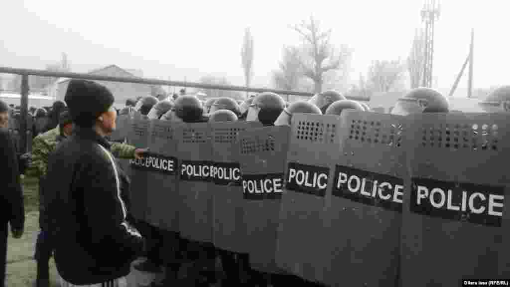 Житель села Бурыл стоит перед полицейским оцеплением.