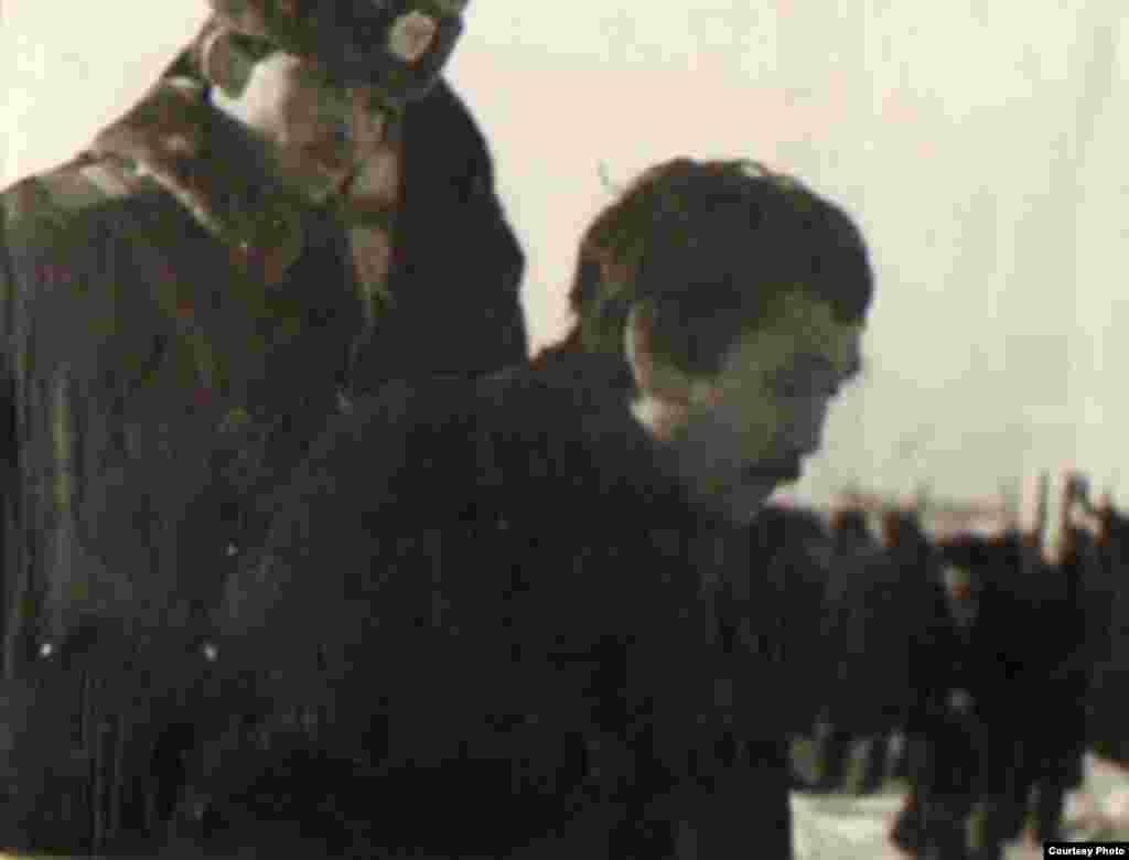 Полиция алаңға келген жастардың бірін ұстап әкетіп бара жатыр.