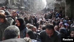 Сирийцы в очереди за гуманитарной помощью, предоставляемой ООН. Северная часть Дамаска, 31 января 2014 года.
