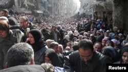 Residents wait to receive food aid distributed by the UN at the Yarmouk camp, south of Damascus, on January 31, 2014.