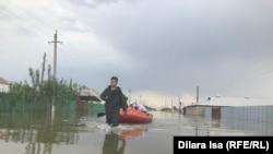 Спасатели помогают жителям Оргебаса добраться к домам на лодке, чтобы забрать документы.