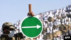 Полиция қызметкері қажылыққа келгендерге Арафат тауына бағыт көрсетіп тұр. Мекке, Сауд Арабиясы, 7 желтоқсан 2008 ж.