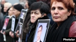 Armenia -- Relatives hold up pictures of Armenians killed in the March 2008 clashes in Yerevan during an opposition rally.