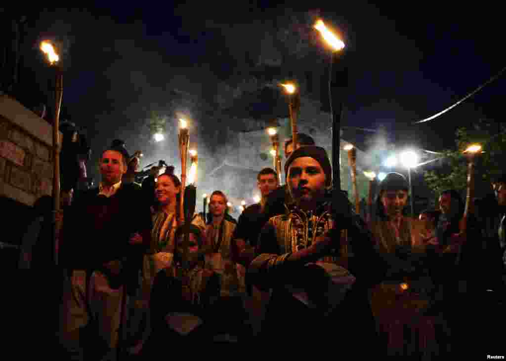 People in folk costumes hold torches during a procession the night before the wedding in the village of Galicnik.