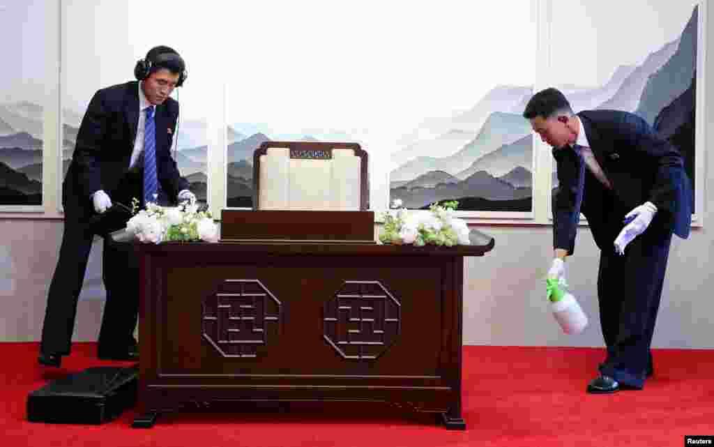 Северокорейские офицеры службы безопасности проверяют и готовят стол, прежде чем северокорейский лидер Ким Чен Ын подпишет гостевую книгу в Доме мира в Пханмунджоме
