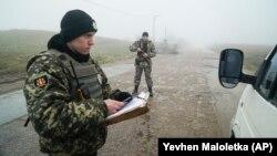 Украинский пограничник проверяет документы на пункте пропуска в Бердянске, 27 ноября 2018