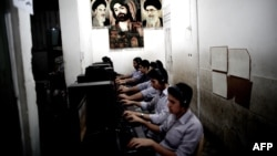 Young Iranians play at a game net arcade decorated with carpets with portraits of the late founder of Islamic republic, Ayatollah Ruhollah Khomeini, Supreme Leader Ayatollah Ali Khamenei, and an Islamic religious portrait, in the city of Qom.