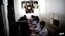Молодые люди в Иране в компьютерном клубе, на стене которого висит портрет аятоллы Али Хаменеи.