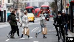 شماری از ساکنان لندن که خریداری کرده اند بخاطر همهگیری ویروس کرونا ماسک صورت پوشیده اند December 22, 2020