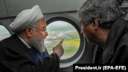 Iranian President Hassan Rohani (L) is seen in a helicopter inspecting the flood-affected villages in Golestan province, March 27, 2019