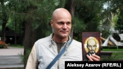 Журналист Дмитрий Шишкин держит в руках свое первое литературное произведение — роман «Восстание». Алматы, 5 сентября 2015 года.