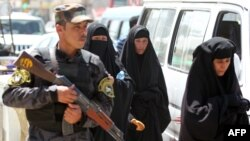 A police officer stands guard as Shi'ite Muslim women walk to the Kadhimiya area of north Baghdad.