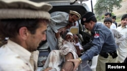 Relatives and police assist a man, who was injured in a suicide attack in a village of Kacha Pakha near Kohat on April 17.