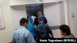 В глубине лифта кардиологического центра в Алматы— один из конвойных, ближе (в белой майке) фигурант дела о «пропаганде терроризма» Жулдызбек Таурбеков, еще ближе - человек в штатском, руководивший действиями конвойных, еще ближе — еще один конвойный. Алматы, 6 июля 2019 года.
