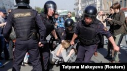 Russian policemen detain opposition supporters during a protest rally in Moscow on May 5.