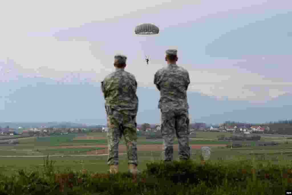 Two soldiers watch as U.S. troops conduct parachute training exercises to keep soldier's skills fresh at Camp Bondsteel in Kosovo. (epa/Valdrin Xhemaj)