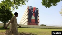 A man walks past a giant portrait of Pakistani Prime Minister Nawaz Sharif (L) and Chinese President Xi Jinping displayed on a building in Islamabad, April 21.