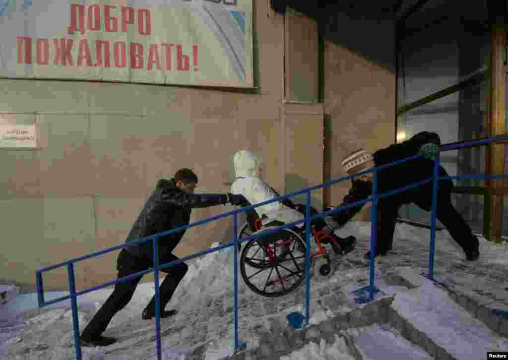"""A participant is helped into the venue of the """"Beauty Without Limits"""" beauty contest for women confined to wheelchairs in Russia's city of Vladivostok. The contest, organized by a local social group Kovcheg, is open to wheelchair users from Russia's Far Eastern Primorsky region. (Reuters/Yuri Maltsev)"""