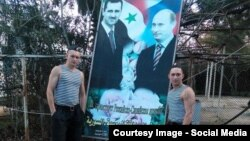 Орусиялык жоокерлер Путин менен Башар Асаддны сүрөтүнүн жанында турат