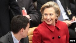 U.S. Secretary of State Hillary Clinton speaks with her British counterpart David Miliband at the NATO meeting in Brussels.