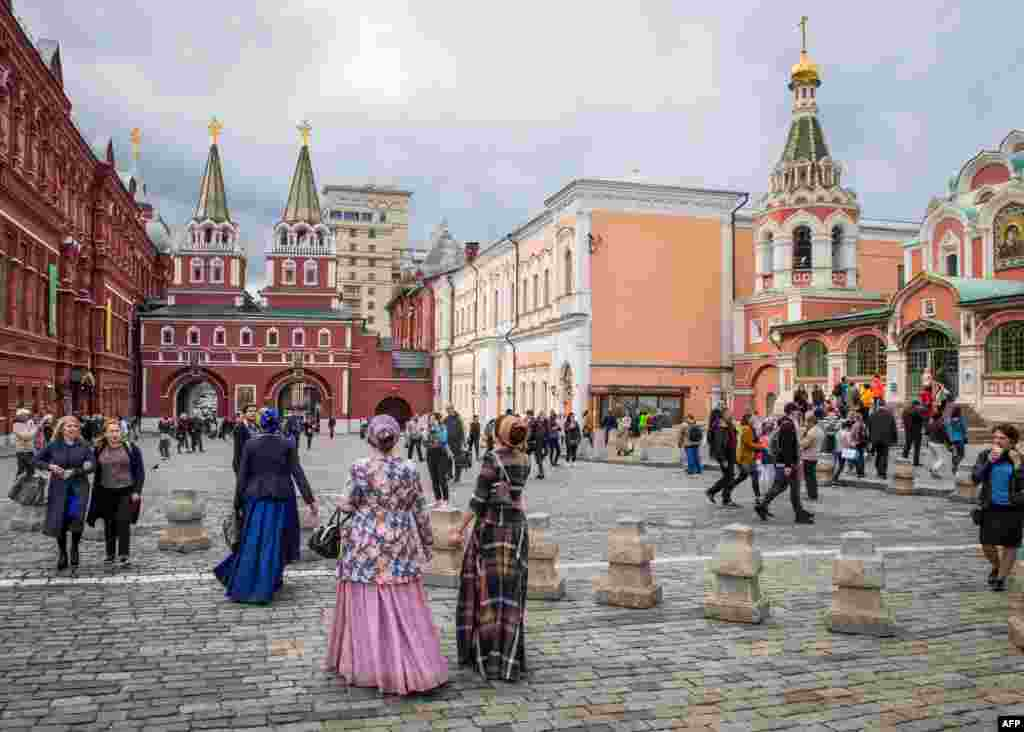 Tourists in traditional dresses walk towards Voskresenskiye Vorota (Resurrection Gates) as they leave Moscow's  Red Square. (AFP/Mladen Antonov)