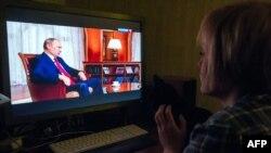 """Ресей телеарнасынан """"Қырым. Отанға қайту жолы"""" деп аталатын деректі фильм көріп отырған адам. 15 наурыз 2015 жыл."""