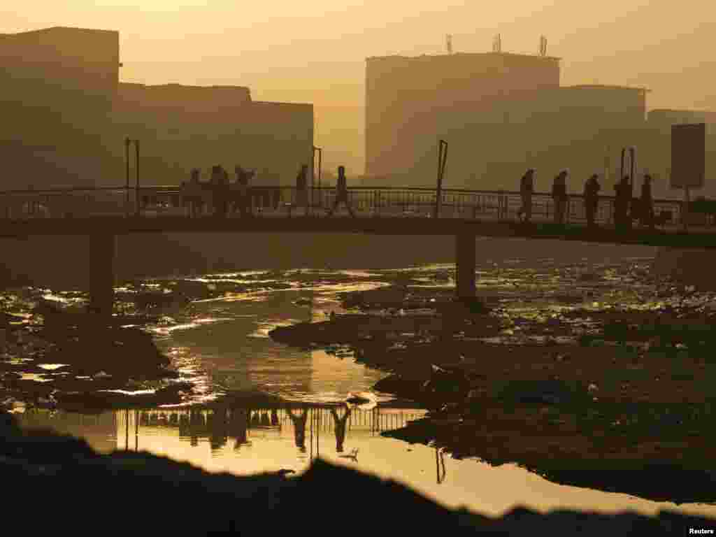 Afghans heading to work cross a bridge over the Kabul River on November 29. Photo by Ahmad Masood for Reuters