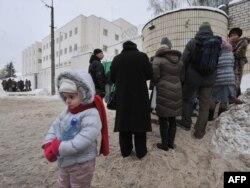 Ребенок стоит возле очереди людей, которые принесли передачи в тюрьму. Минск, 23 декабря 2010 года.