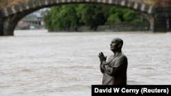 Наполовину затопленная статуя проповедника и общественного деятеля Шри Чинмоя в Праге
