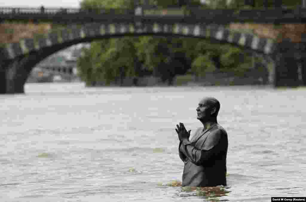In the Czech capital, Prague, a statue of Indian spiritual leader Sri Chinmoy is partially submerged in water from the rising Vltava River on June 2.